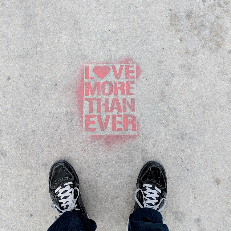sidewalk art reading 'love more than ever'