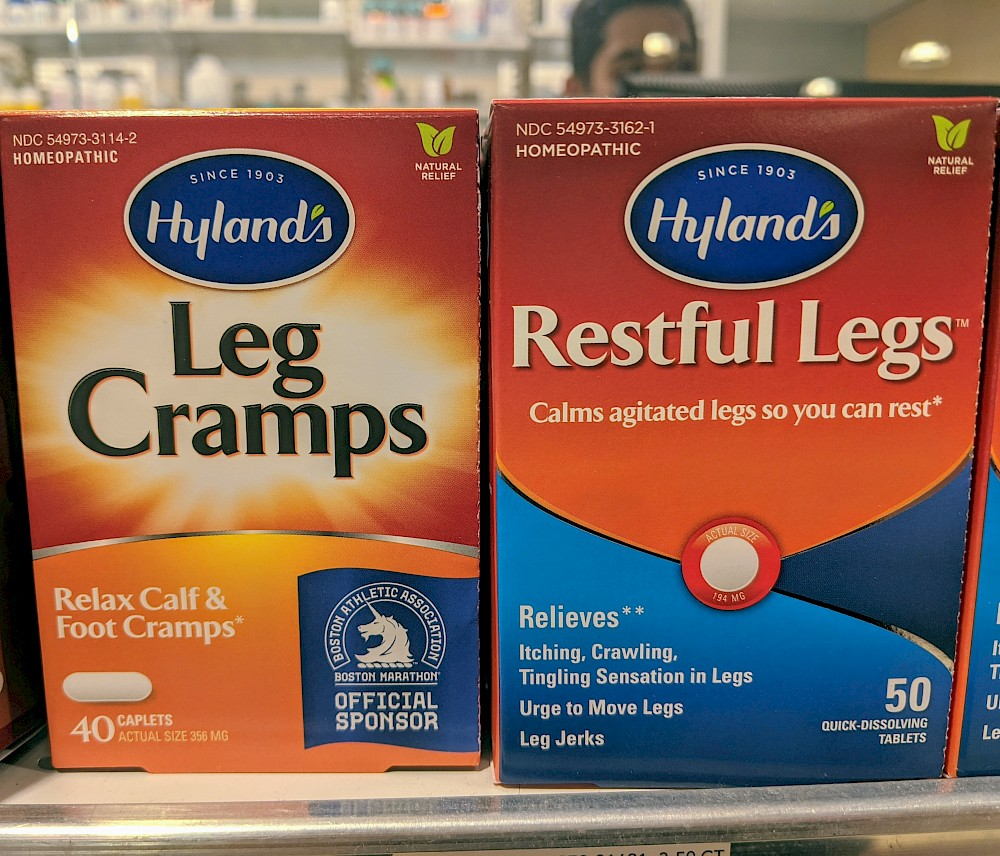 two boxes of medicine; left one labeled 'Leg Cramps' and right one labeled 'Restful Legs'