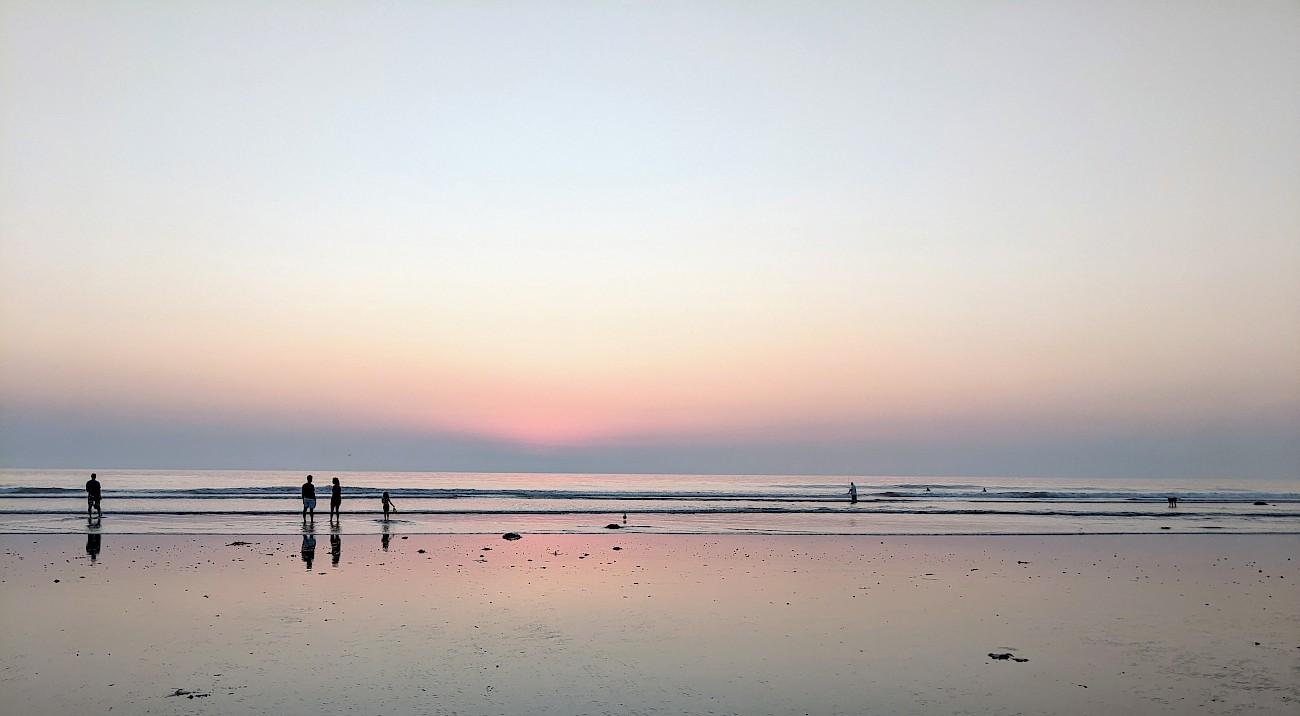 pink sky just after sunset reflected in the wet sand