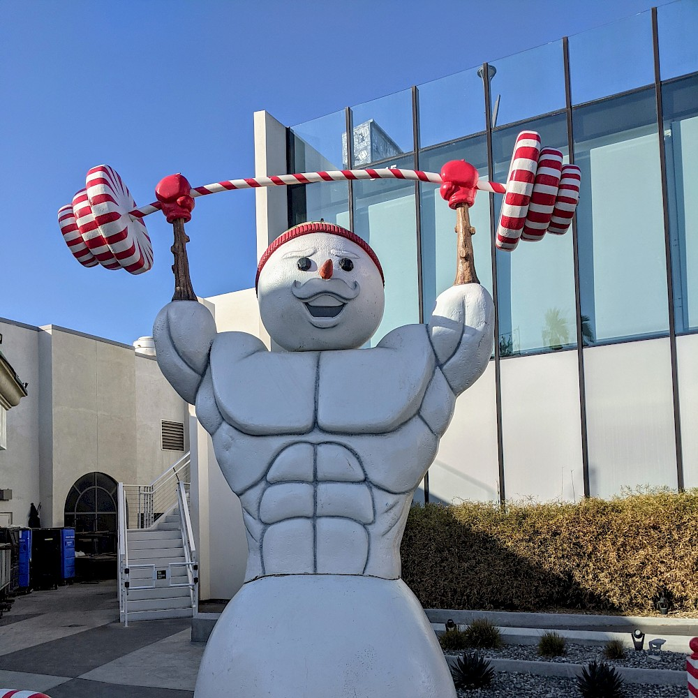 statue of a muscular snowman lifting weights